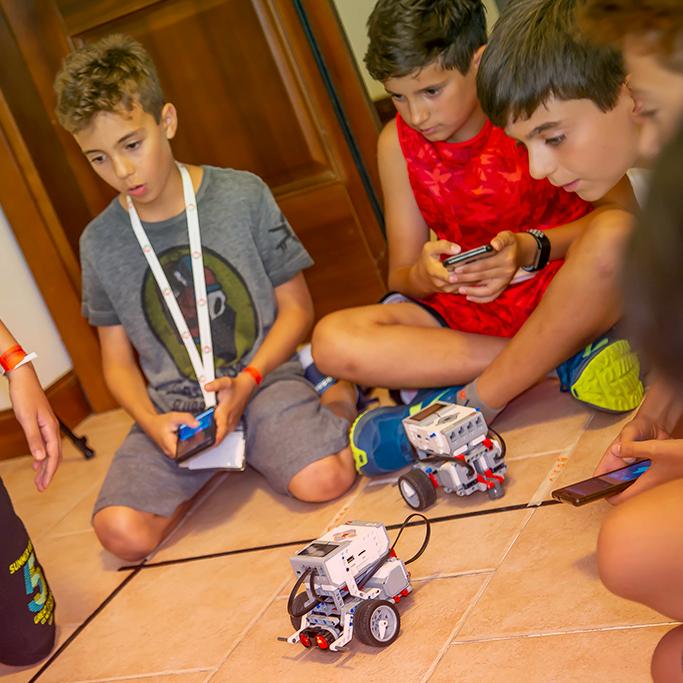 Ragazzi programmano gli Mbot durante uno STEAMcamp